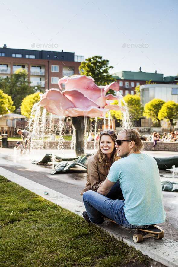 Happy woman sitting with man on skateboard at park in city - Stock Photo - Images