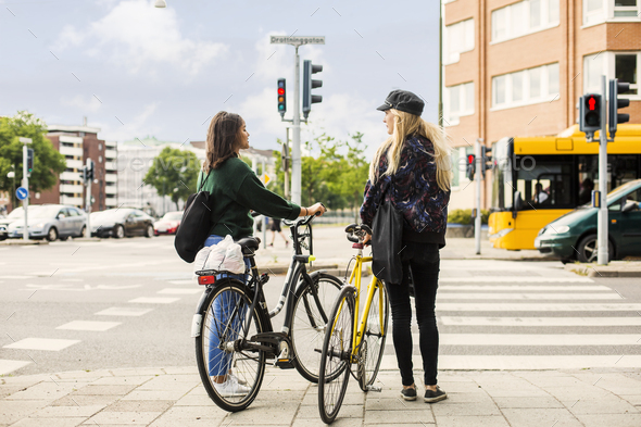 Two young women pushing bikes in town - Stock Photo - Images