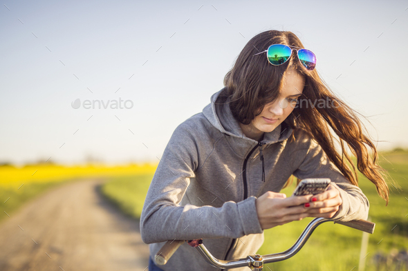 Woman on bicycle texting on mobile phone - Stock Photo - Images