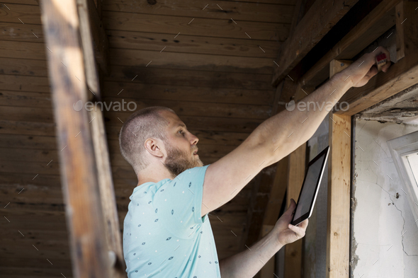 Man working on renovating old attic with tablet - Stock Photo - Images