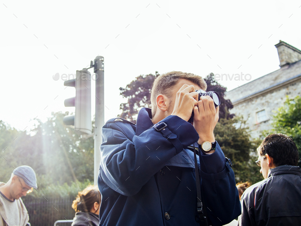 Man photographing in city against clear sky - Stock Photo - Images