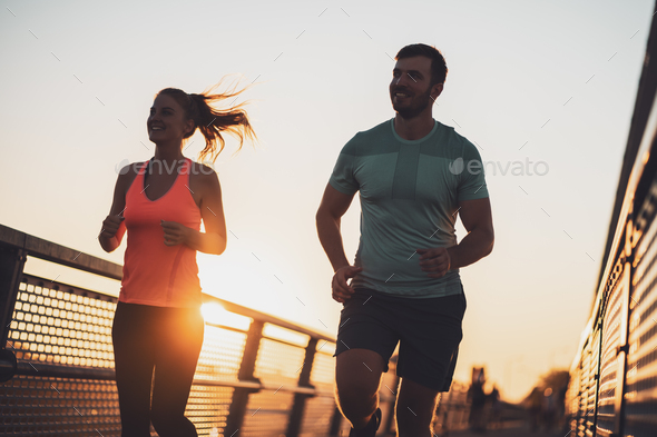 Happy couple jogging in sunset - Stock Photo - Images