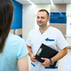 Male doctor talks with patient in clinic corridor - PhotoDune Item for Sale