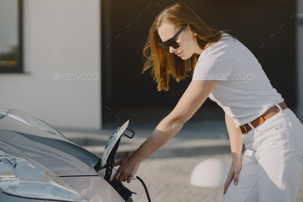 Woman charging electro car at the electric gas station - Stock Photo - Images