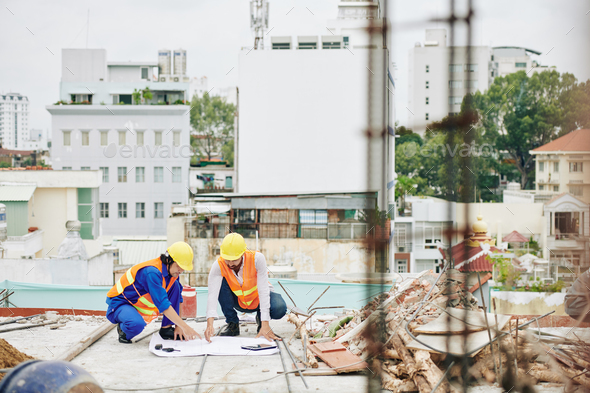 Builders discussing plan of works - Stock Photo - Images
