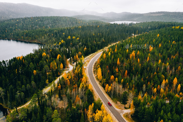 Aerial view of rural road with red car in yellow and orange autumn forest with blue lake - Stock Photo - Images