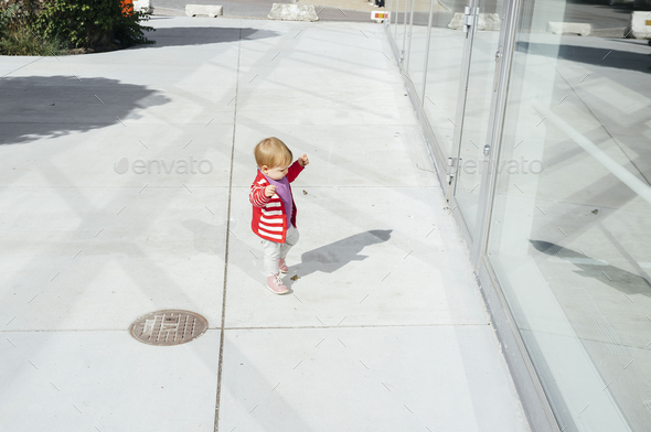 Full length of baby girl standing outside glass building - Stock Photo - Images