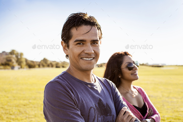 Portrait of happy man with girlfriend at park against sky - Stock Photo - Images