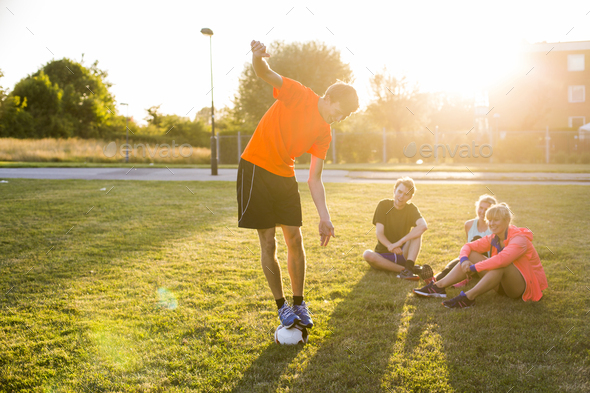 Sporty friends looking at man balancing on soccer ball at park - Stock Photo - Images