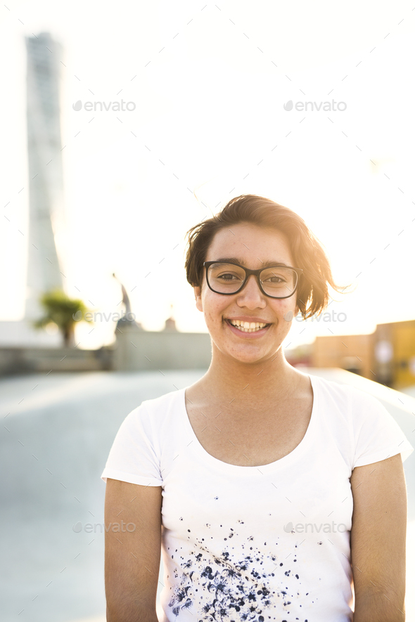 Portrait of smiling teenage girl wearing glasses at skate park - Stock Photo - Images