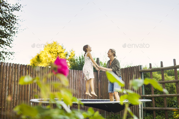Mother and daughter jumping on trampoline in garden - Stock Photo - Images