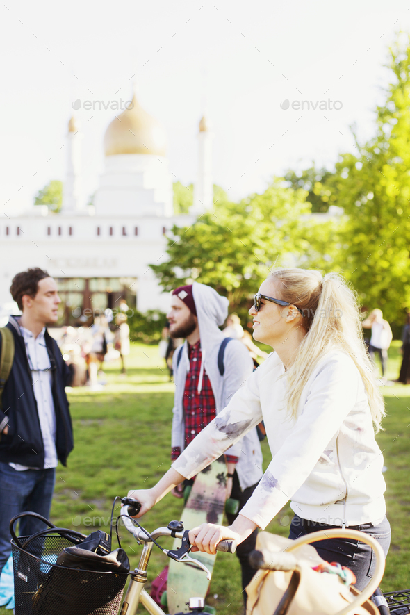 Woman holding bicycle while standing with friends at park - Stock Photo - Images