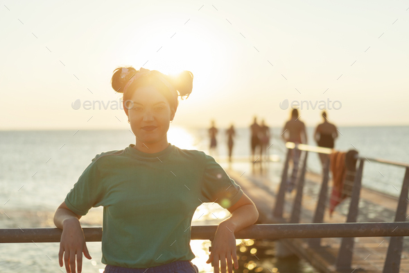 Portrait of confident young woman leaning on railing at pier over sea - Stock Photo - Images