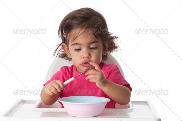 Curious baby girl is testing her fork - Stock Photo - Images
