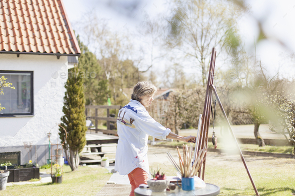 Side view of senior female artist painting in backyard - Stock Photo - Images