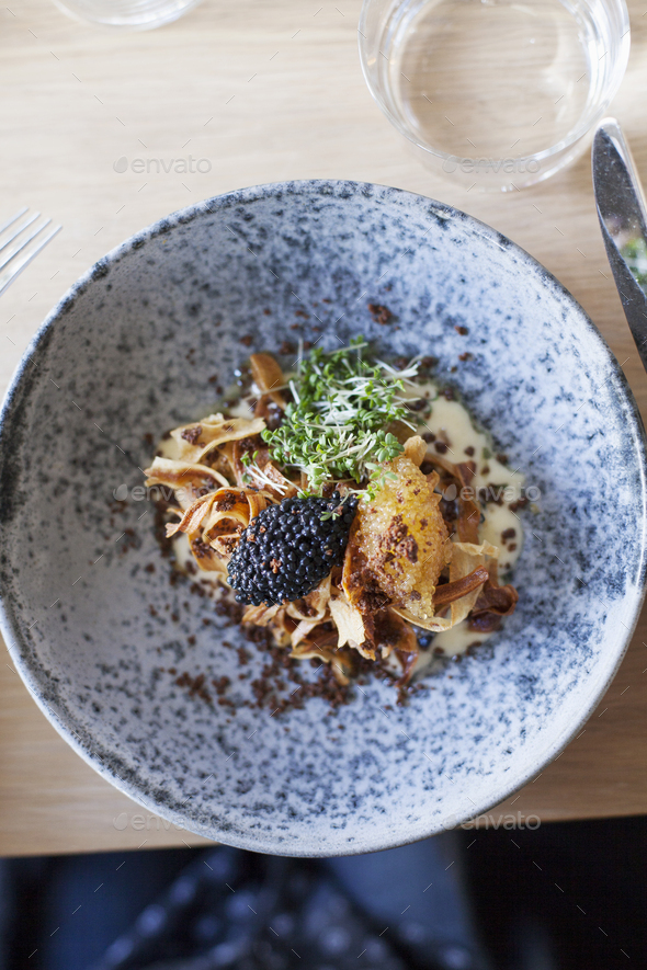 Directly above shot of avruga and coal fired salsify served on restaurant table - Stock Photo - Images