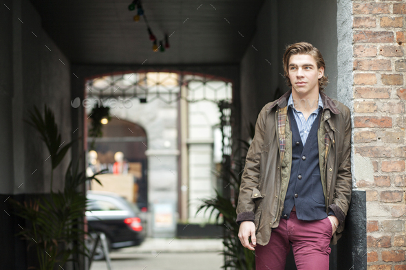 Thoughtful young man leaning on wall outdoors - Stock Photo - Images
