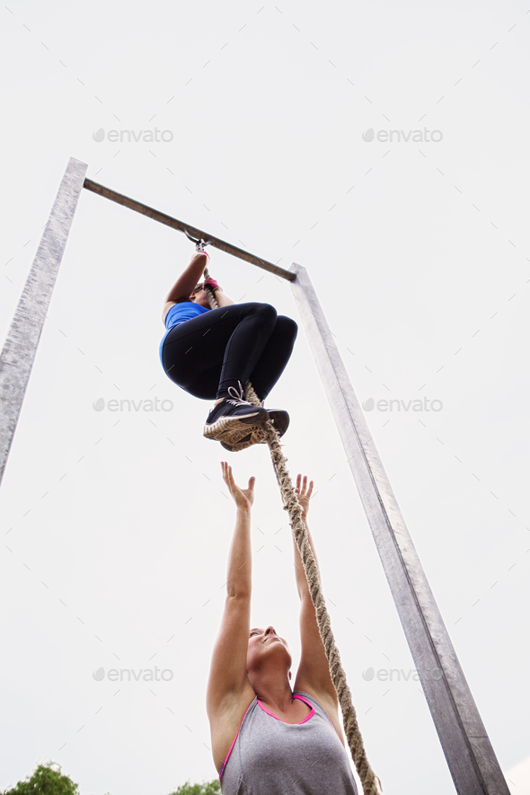Low angle view of woman motivating friend climbing rope against clear sky - Stock Photo - Images