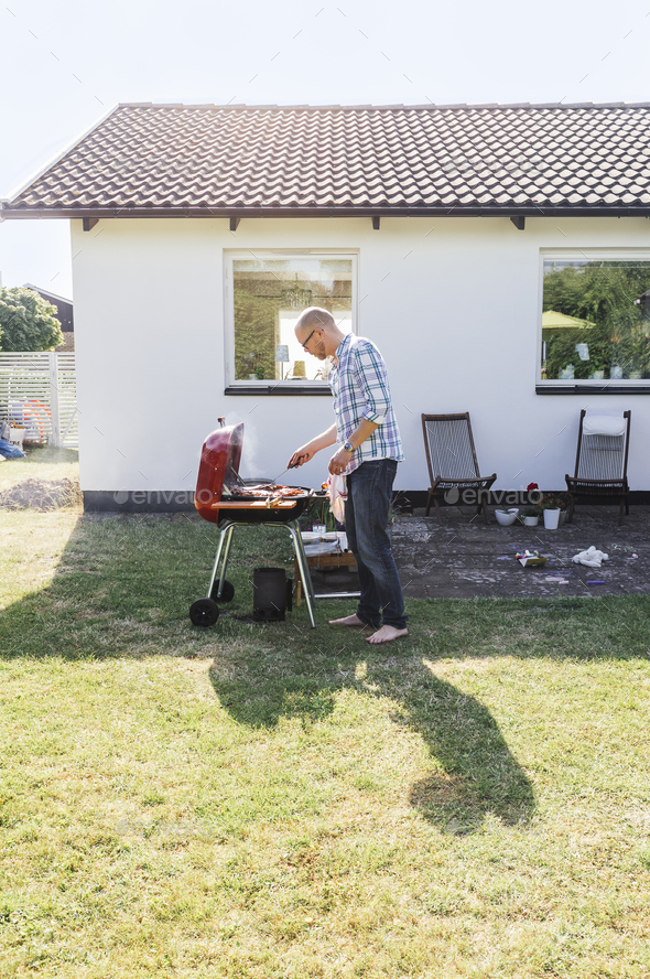 Full length of man grilling food outside house - Stock Photo - Images