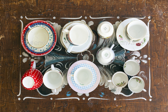 Top view of various tea cups and saucers on wooden table - Stock Photo - Images