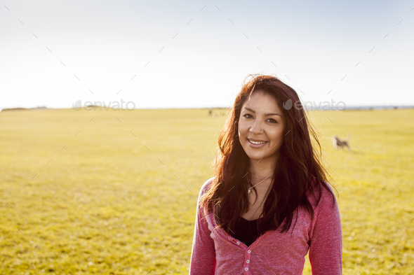 Portrait of smiling woman at park on sunny day - Stock Photo - Images