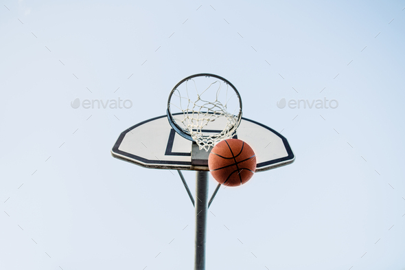 Low angle view of basketball hoop with ball against clear sky