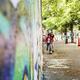 Teenage girls skateboarding at footpath by wall - PhotoDune Item for Sale