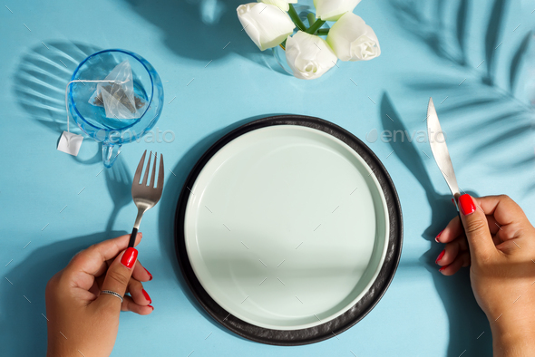 Dinner table with ceramic plate and woman hand holding knife and fork - Stock Photo - Images