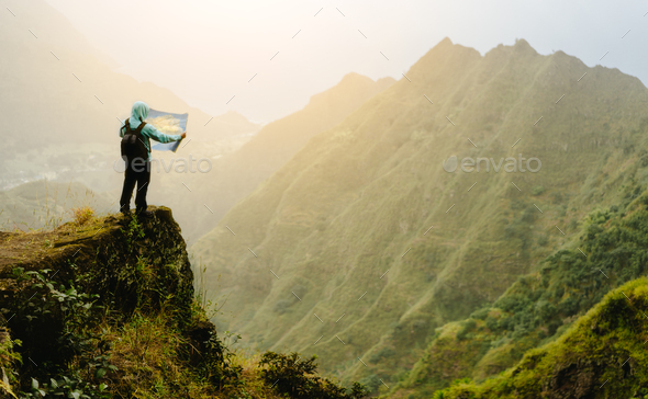 Man with the map staying on top of the mountain rock with gorgeous panorama view over high mountain - Stock Photo - Images