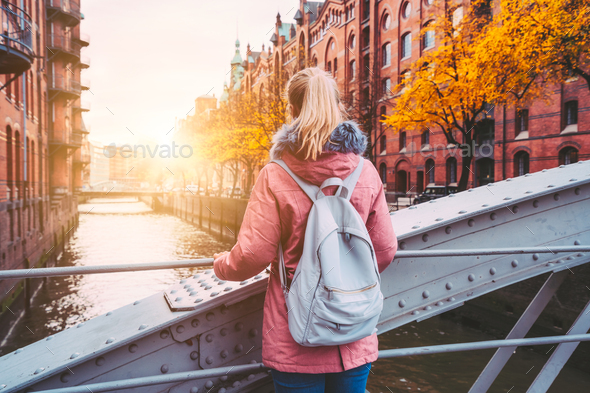 Back rear view of adult blond woman tourist with backpack enjoying autumn beautiful sunset scene on - Stock Photo - Images