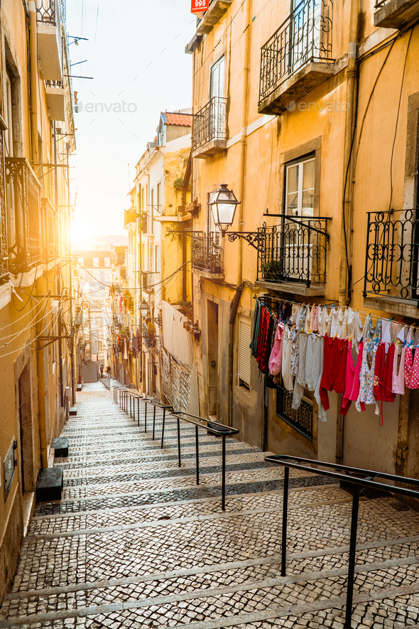 Staircase in the cobblestone street in Lisbon. Hanging laundry in typical narrow street. Sunset in - Stock Photo - Images