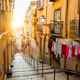 Staircase in the cobblestone street in Lisbon. Hanging laundry in typical narrow street. Sunset in - PhotoDune Item for Sale