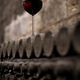 glass with red wine on aged wine bottles in vintage wine cellar - PhotoDune Item for Sale