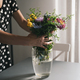 woman arranging a bouquet of flowers in a glass vase - PhotoDune Item for Sale