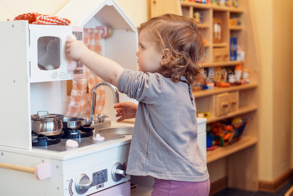 toddler girl playing toy kitchen - Stock Photo - Images