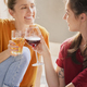 Two friends spending time together drinking wine and juice - PhotoDune Item for Sale