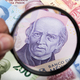 Mexican Pesos in a magnifying glass - PhotoDune Item for Sale