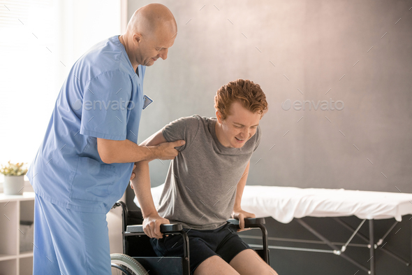 Bald clinician in uniform helping young man to sit in wheelchair after training - Stock Photo - Images