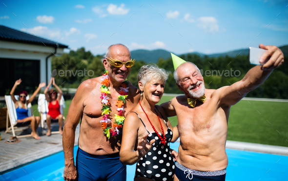 Group of cheerful seniors by swimming pool outdoors in backyard, taking selfie - Stock Photo - Images
