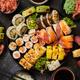Asian food fest. Menu sushi with nigiri, maki, uramaki on black plates. Various kinds of sushi - PhotoDune Item for Sale