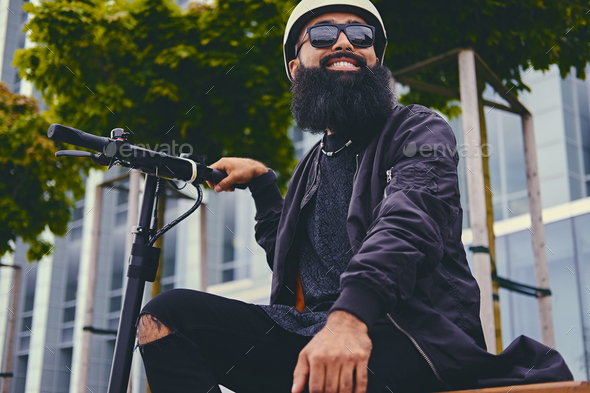 A man relaxing on a bench after riding by electric scooter. - Stock Photo - Images