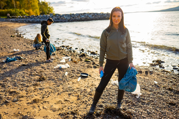 Smiling young woman cleaning beach with volunteers during sunset - Stock Photo - Images