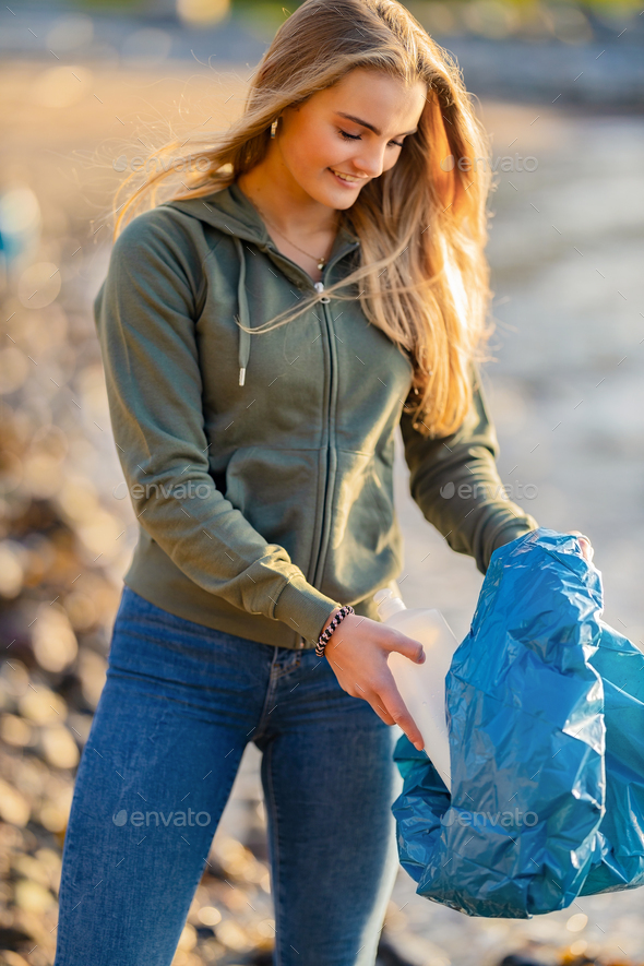 Smiling Young Female Volunteer holding bottle and garbage bag at beach - Stock Photo - Images
