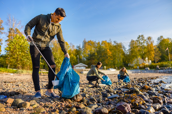 Man cleaning beach with volunteers on sunny day - Stock Photo - Images