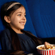 Little smiling girl eating popcorn in cinema - PhotoDune Item for Sale