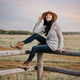 Girl in a hat sits on a farm fence.  Countryside. Prairies - PhotoDune Item for Sale
