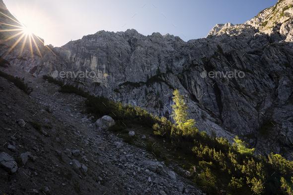 sunrise behind mountain peak - Stock Photo - Images