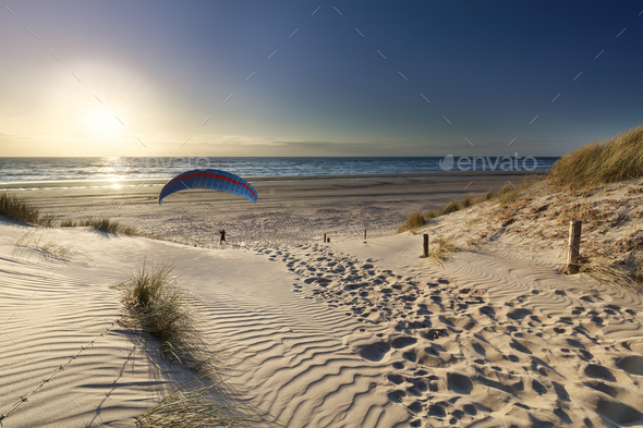 man paragliding on beach at sunset by sea - Stock Photo - Images