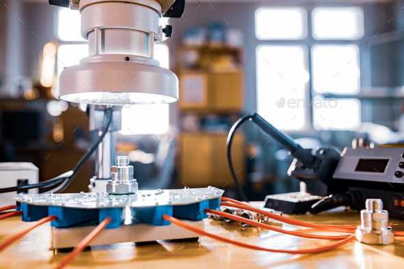 Modern microscope, connectors component and large green microcircuit in workshop laboratory - Stock Photo - Images