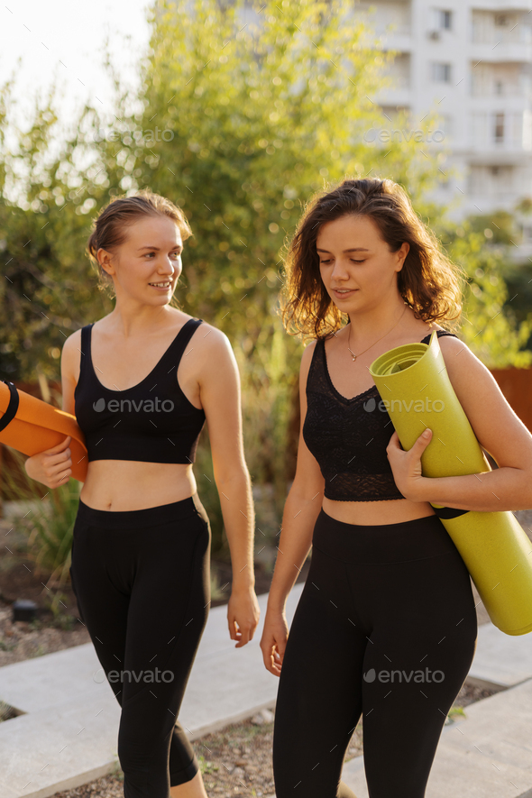 Two young beautiful women in sportswear going to do sports training, gymnastics, yoga - Stock Photo - Images